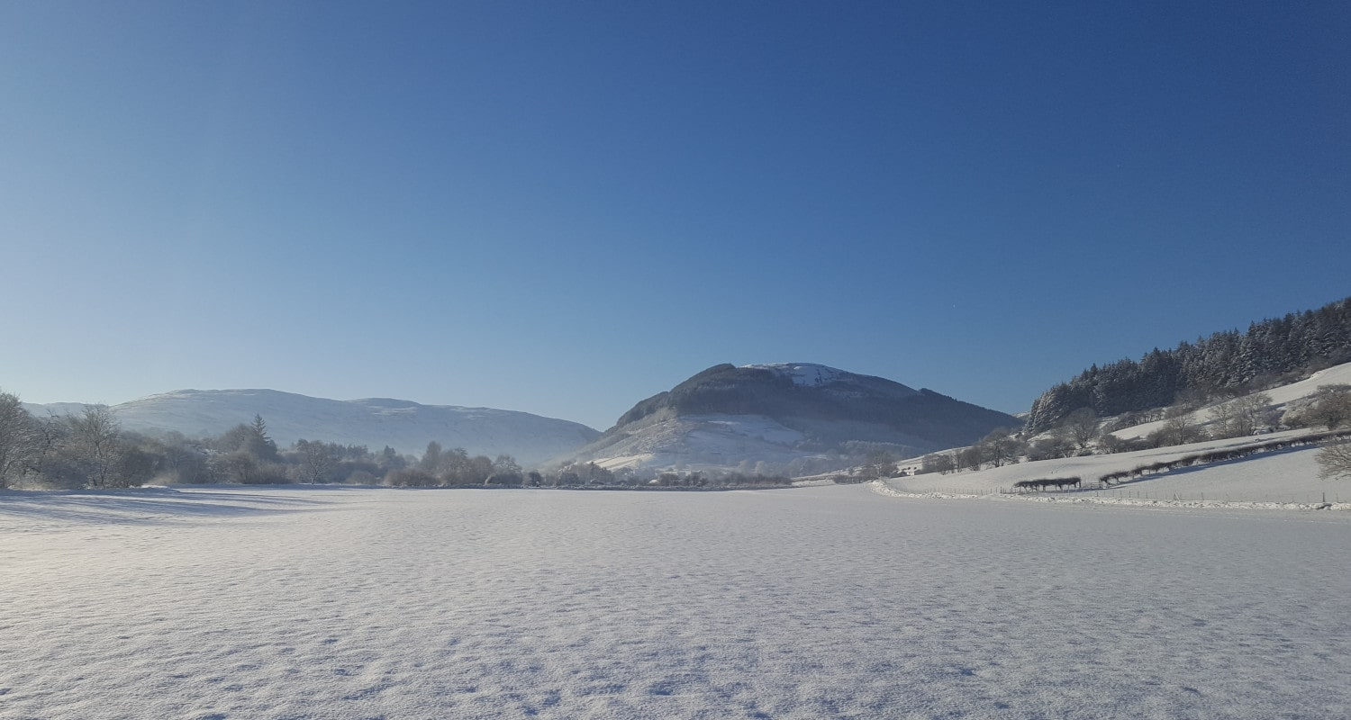 Snow-covered fields leading to the village of Penmachno